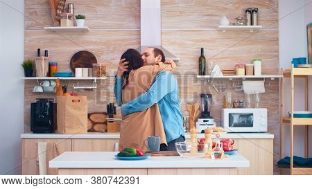 Cheerful Couple Smiling And Dancing In Kitchen. Romantic Husband And Wife. Cheerful Happy Young Fami