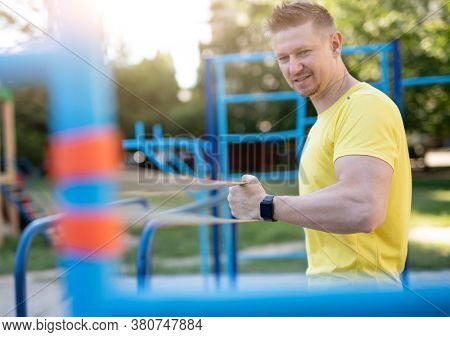 Sportive man training with resistance band outdoors in park