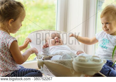 Three Little Kids Play Near The Window. Brothers And Sister With The Baby.toddler Kid Meeting Newbor