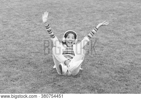 Kid Girl Enjoy Music Green Grass Meadow. Happiness Is Not Something You Sit Back And Wait. Listen Mu