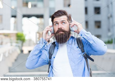 We Have Our Ears In The Streets. Bearded Man Wear Ear Phones Outdoors. Hipster Listen To Music In He