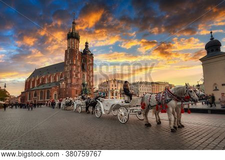 Krakow, Poland - November 12, 2017: Horse carriages at the Main Square in Krakow, Poland. Krakow is the second largest and one of the oldest cities in Poland.
