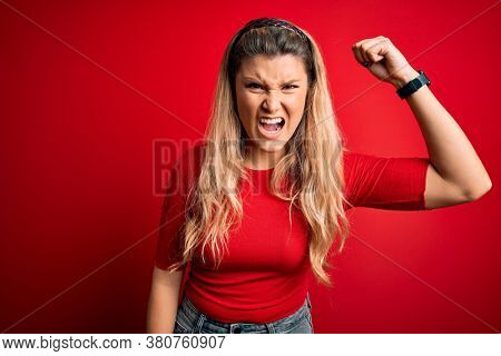 Young beautiful blonde woman wearing casual t-shirt standing over isolated red background angry and mad raising fist frustrated and furious while shouting with anger. Rage and aggressive concept.
