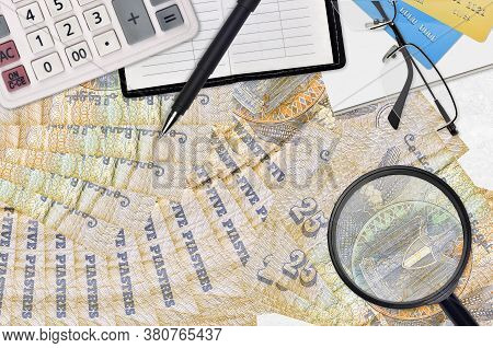 25 Egyptian Piastres Bills And Calculator With Glasses And Pen. Tax Payment Season Concept Or Invest