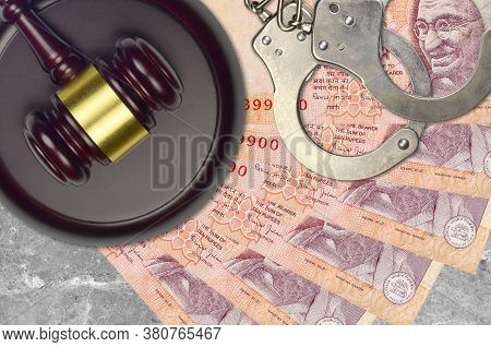 10 Indian Rupees Bills And Judge Hammer With Police Handcuffs On Court Desk. Concept Of Judicial Tri