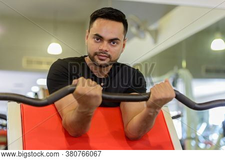Young Bearded Indian Man Lifting Weights At The Gym