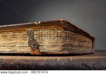 A Fragment Of An Ancient Brown Book With Clasps And Yellow Pages On An Old Wooden Table.