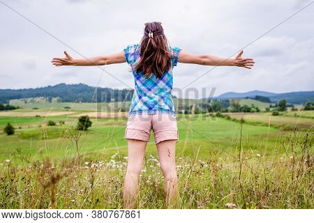 Beautiful Woman In Nature With Arms Outstretched. Happy People Lifestyle. Vacation In Nature Lifesty