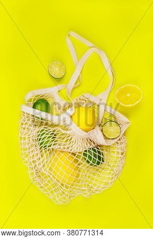 Bright Summer Citrus Flatlay With Lemons And Limes In The String Mesh Bag Isolated On Yellow Backgro