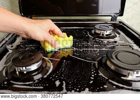 Woman Cleans Gas Stove With A Washcloth And Foam, Surface Cleaning, Cleaning The Kitchen, Kitchen Ap