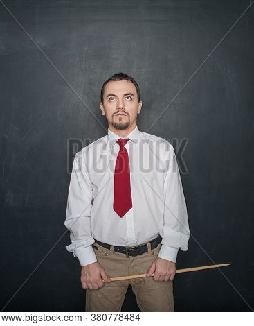Thoughtful Teacher With Pointer Looking Up On Blackboard