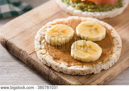 Puffed Rice Cake With Banana And Peanut Butter On Wooden Table.