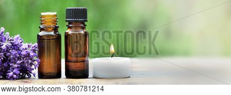 Bottles Of Essential Oil With Lavender Flower And Canddle Arranged On A Wooden Table On Green Backgr
