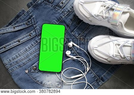 Flatlay Of Hipster Stylish Modern White Sneakers, Smart Phone With Green Screen Chromakey And Headph