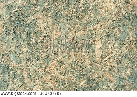 Pale Blue Tinted Background Of Compressed Wood Chippings Used As A Building Material Panel