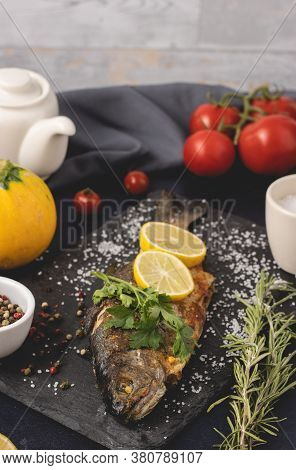 Grilled Trout With Olive Oil, Parsley, Pepper, Salt And Lemon Placed On The Dark Background. Healthy