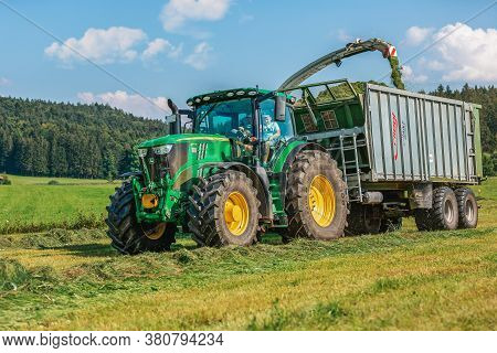 Bavaria / Germany - August 07,2020: Claas Jaguar 930 Harvester And A John Deere 6175r With A Fliegl