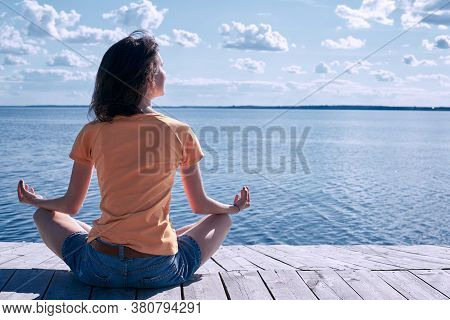 Back View Of A Young Woman Enjoying Sea View Sitting On A Wooden Seafront In Lotus Position