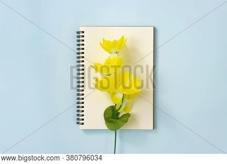 Spiral Notebook Or Spring Notebook In Unlined Type And Yellow Flowers At Center On Blue Pastel Minim