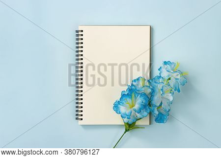 Spiral Notebook Or Spring Notebook In Unlined Type And Blue Flowers At Bottom Right On Blue Pastel M