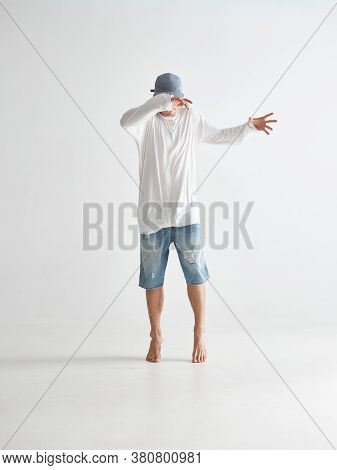 Stylish Young Guy Breakdancer In Cap Covering Face With Hands Stands On Tiptoes Barefoot In Studio O