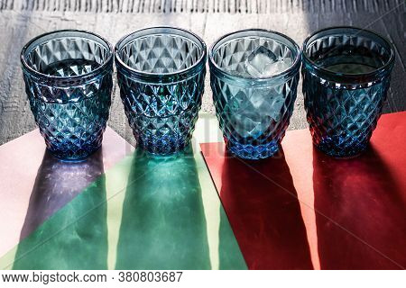 Set of four patterned blue glasses of water with ice or cocktails with long shadows on colorful paper and black background. Long harsh shadows. Refreshment on hot day concept photo.