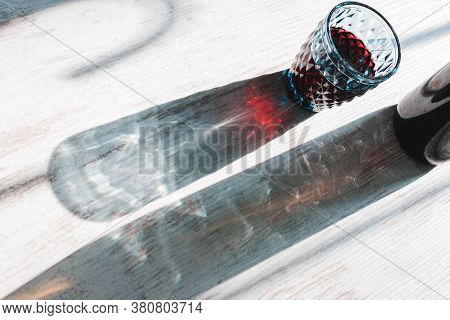 Sparkling glimmering color long shadows and light play of crystal blue red wine glass and bottle optical effect on white wood background. Harsh day light. High angle diagonal view with space for text.