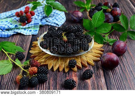 Fresh Berries And Leaves Of Bramble  And Purple Ripe Plums On A Brown Wooden Background. Still Life.