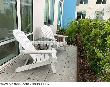 Two Adirondack Chairs Sitting On A Patio.  Concept Peaceful, Mindful, Relaxation, And Relaxed Lifest