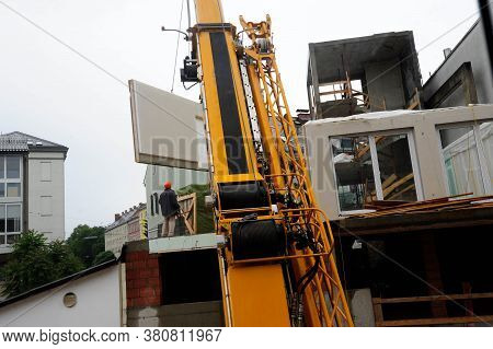 Worker Next To Heavy Machinery At The Construction Of A Prefabricated House