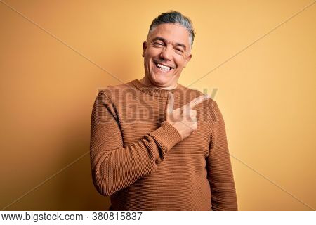Middle age handsome grey-haired man wearing casual sweater over yellow background cheerful with a smile of face pointing with hand and finger up to the side with happy and natural expression on face