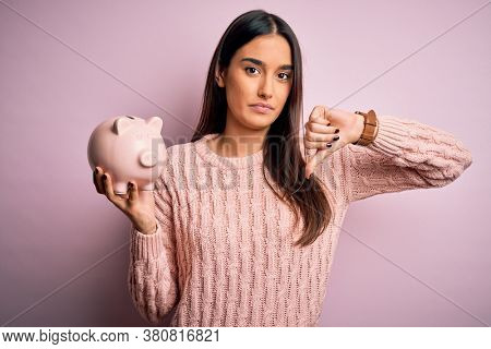 Young beautiful brunette woman holding piggy bank saving money for retirement with angry face, negative sign showing dislike with thumbs down, rejection concept