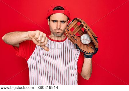 Young handsome sporty man with blue eyes playing baseball using glove and ball with angry face, negative sign showing dislike with thumbs down, rejection concept