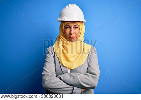 Middle age brunette architect woman wearing muslim traditional hijab and security helmet skeptic and nervous, disapproving expression on face with crossed arms. Negative person.