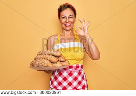 Middle age senior housewife pin up woman wearing 50s style retro dress cooking wholemeal bread doing ok sign with fingers, excellent symbol