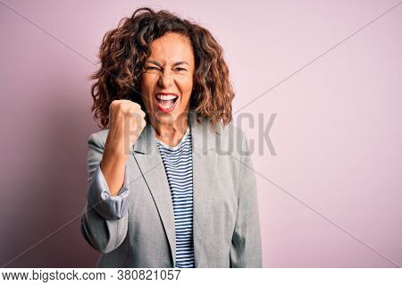 Middle age beautiful businesswoman wearing elegant jacket over isolated pink background angry and mad raising fist frustrated and furious while shouting with anger. Rage and aggressive concept.