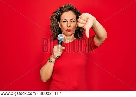 Middle age senior singer woman singing using music microphone over red background with angry face, negative sign showing dislike with thumbs down, rejection concept