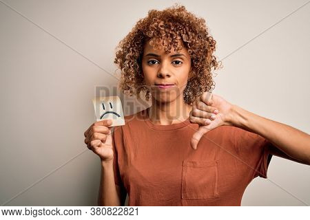 Young african american woman with curly hair holding reminder paper with sad face emoji with angry face, negative sign showing dislike with thumbs down, rejection concept