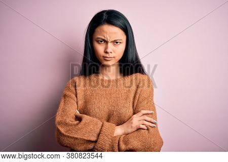 Young beautiful chinese woman wearing casual sweater over isolated pink background skeptic and nervous, disapproving expression on face with crossed arms. Negative person.