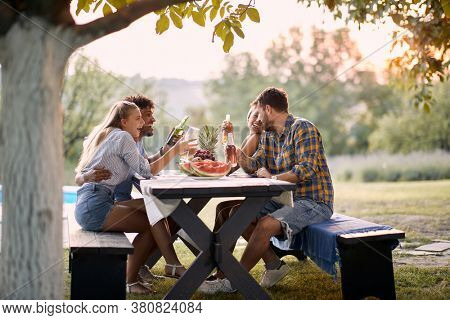 Group of young multi-ethnic friends having fun outdoor, talking and laughing