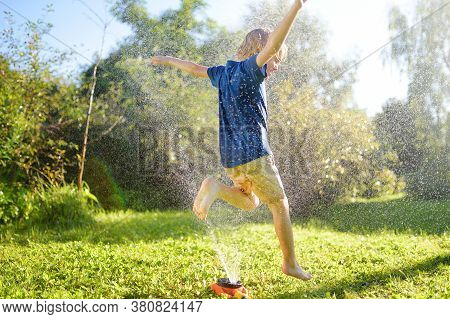 Funny Little Boy Playing With Garden Sprinkler In Sunny Backyard. Preschooler Child Laughing, Jumpin