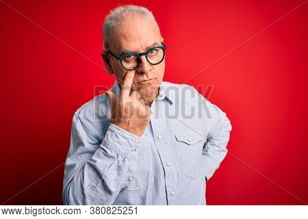 Middle age handsome hoary man wearing casual striped shirt and glasses over red background Pointing to the eye watching you gesture, suspicious expression