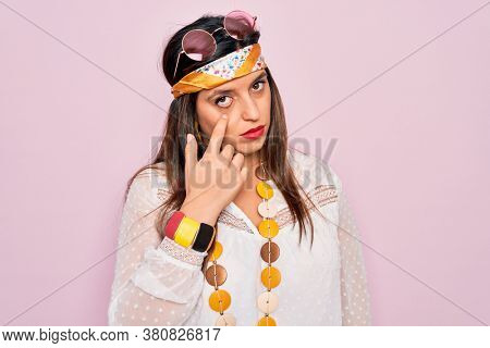 Young hispanic hippie woman wearing fashion boho style and sunglasses over pink background Pointing to the eye watching you gesture, suspicious expression