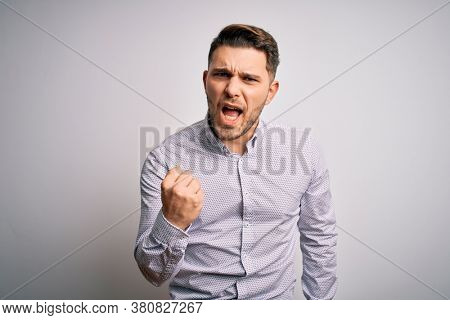Young business man with blue eyes standing over isolated background angry and mad raising fist frustrated and furious while shouting with anger. Rage and aggressive concept.