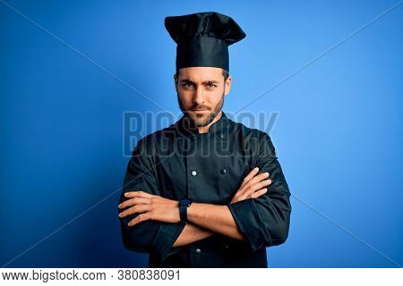 Young handsome chef man with beard wearing cooker uniform and hat over blue background skeptic and nervous, disapproving expression on face with crossed arms. Negative person.