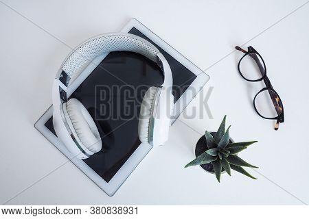 White Wireless On A White Tablet, Glasses And A Flower On A White Table. Wilde On Top. Concept Podca