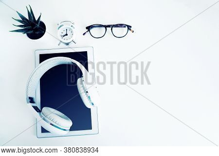 White Wireless Headphones On A White Tablet, Glasses, An Alarm Clock And A Houseplant On A White Tab