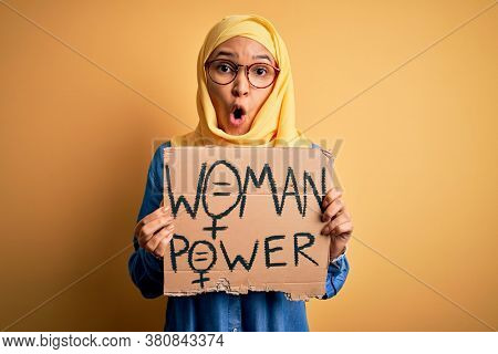Beautiful woman with curly hair wearing muslim hijab asking for women rights holding banner scared in shock with a surprise face, afraid and excited with fear expression