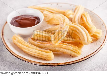 Churros With Powdered Sugar And Chocolate Sauce.