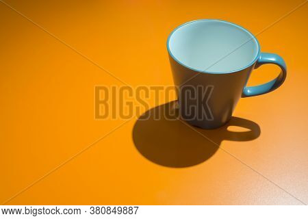 Empty Blue Coffee Cup And Shadow On The Yellow Table With Light Reflection In The Living Room At The